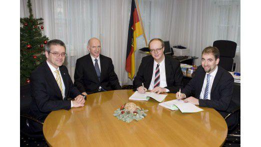 Im Beisein von Hubert Geml (Atos) und Werner Breitbach (BAAINBw) unterzeichnen Bernd Lautemann (BAAINBw) und Jörn Becker (Atos) den Vertrag (v.l.)